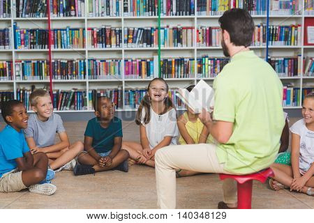 Teacher teaching kids in library at elementary school