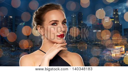 people, luxury and fashion concept - beautiful woman in black with red lips over night singapore city and lights background