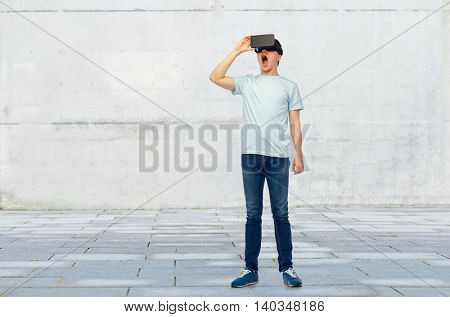 3d technology, virtual reality, entertainment, cyberspace and people concept - amazed young man with virtual reality headset or 3d glasses over street background