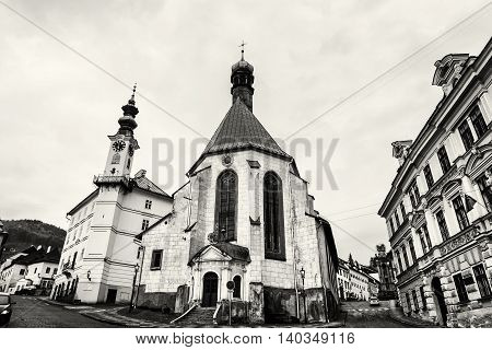 Saint Catherine's church and town hall in Banska Stiavnica city Slovak republic. Black and white photo. Architectural scene. Travel destination. Place for worship. Streets and buildings.