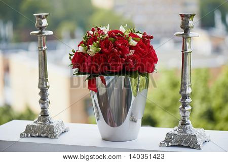 dense red bouquet of roses and berries, brilliant in the iron bucket and two metal candle holders