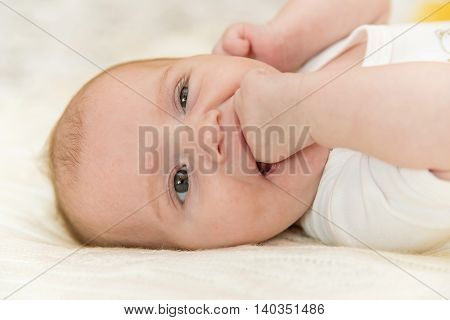 Cute smiling newborn baby 3 months old puts hand into mouth