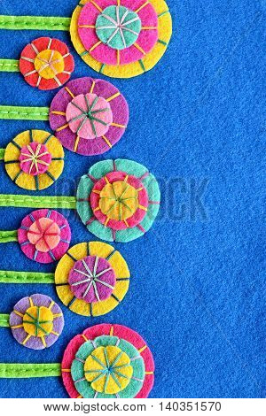 Multicolored flowers on a blue felt sheet. DIY design and decor. Sew on bright flowers. Holiday background. Greeting card for birthday, mother's day, Easter. Colorful summer postcard