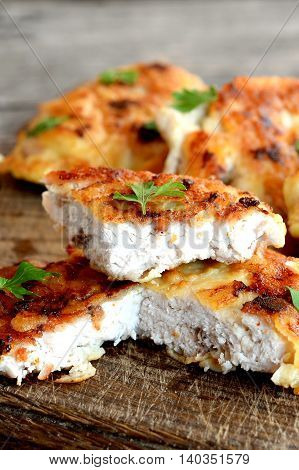 Chopped Turkey steak fried in egg batter and garnished with fresh herbs. Appetizing fried meat slices on a cutting board and an old wooden background. Closeup