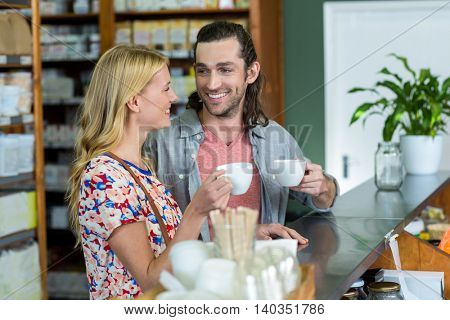 Happy couple interacting with each other while having coffee in supermarket
