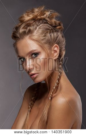 Beauty woman with beautiful make-up color . Brown hair braids of hair clean shiny skin beauty face . Portrait shot in studio on a gray background .