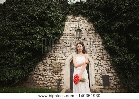 Bride. Beautiful young blond woman in the park with flower wreath and bouquet on a warm summer day.