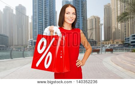 sale, discount, tourism and holidays concept - smiling young woman in red dress with shopping bags with percent sign over dubai city street background