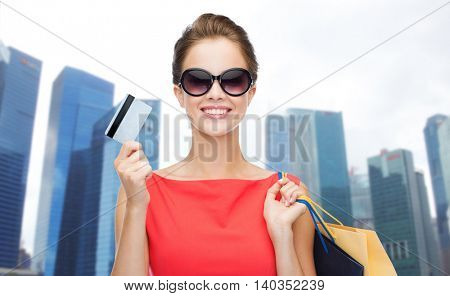 people, holidays, tourism, travel and sale concept - young happy woman with shopping bags and credit card over singapore city skyscrapers background