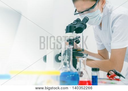 Close Up Of Female Scientist Looking To Microscope In Clinical Laboratory Chemical Formula And Dna M