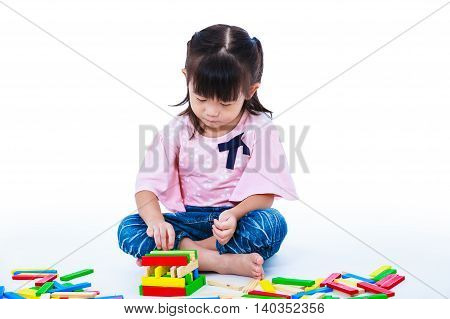 Happy asian child. Pretty girl playing toy wood blocks isolated on white background. Educational toys for kindergarten child. Strengthen the imagination of child. Studio shot.