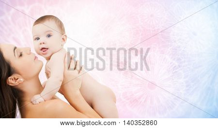 family, motherhood, parenting, people and child care concept - happy mother holding adorable baby over rose quartz and serenity patterned background