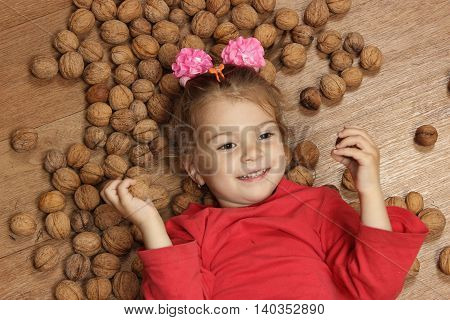 cheerful little girl plays on a floor on a heap of walnuts