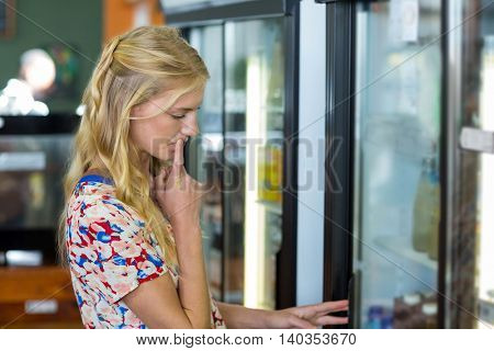 Woman looking in refrigerator in supermarket
