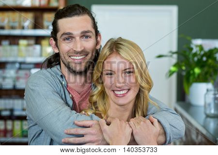 Portrait of happy couple embracing each other in a coffee shop at supermarket