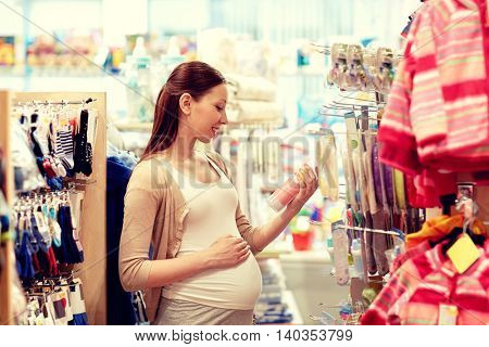 pregnancy, people, sale and expectation concept - happy pregnant woman shopping at children clothing store