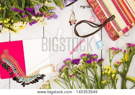 Straw Bag, Colorful Flowers, Notepad, Cosmetics Makeup, Bijou And Essentials On White Wooden Backgro