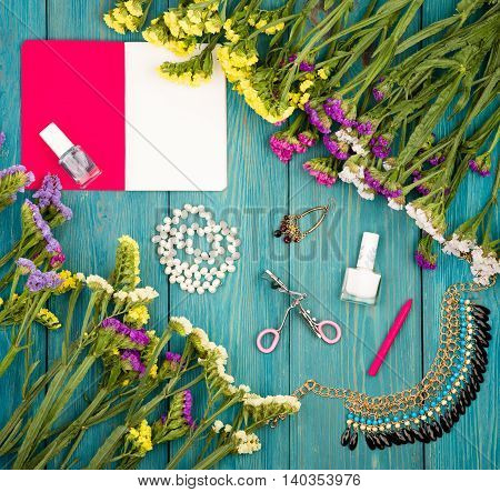 Colorful Flowers, Cosmetics Makeup, Notepad, Bijou And Essentials On Blue Wooden Background