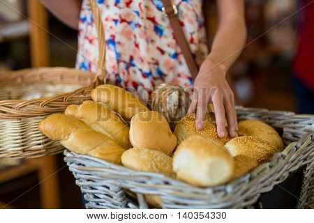 Mid section of woman selecting bread in supermarket