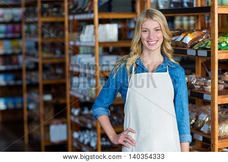Portrait of smiling female staff standing with hand on hip in supermarket