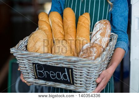 Female staff holding a basket of breads in supermarket
