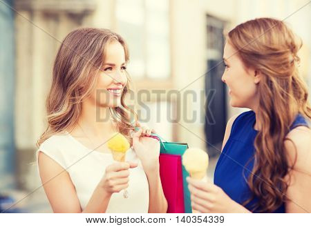 sale, consumerism, summer and people concept - happy young women with shopping bags and ice cream talking on city street