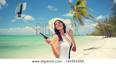 travel, leisure, summer, technology and people concept - sexy young woman taking selfie with smartphone on tropical beach background