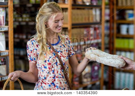 Smiling woman purchasing a loaf of bread in supermarket