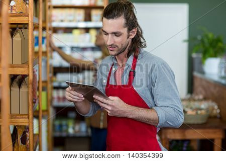 Male staff using a digital tablet in supermarket