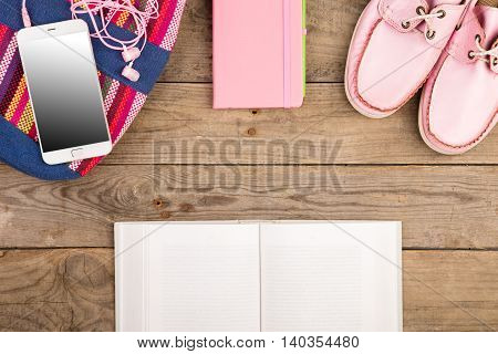 Colorful Bag, Smart Phone, Headphones, Notepad, Blank Book And Pink Shoes On Wooden Desk