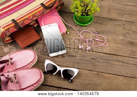 Straw Bag, Smart Phone, Headphones, Sunglasses, Notepad, Pink Shoes And Passport On Wooden Desk