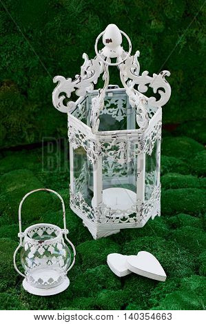 Two white wrought-iron lantern for candles, of different sizes. Two white wooden heart on a background of moss