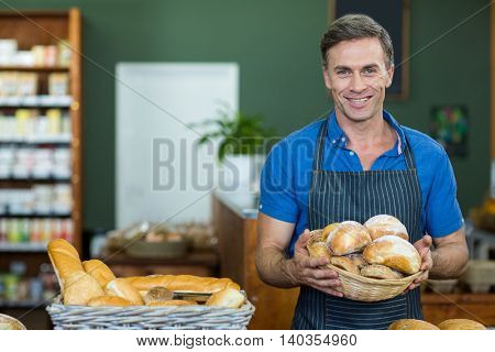 Portrait of male staff holding a basket of bread in supermarket