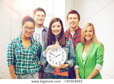 education and time concept - group of students at school with clock