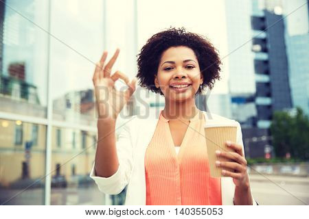 business, drinks, gesture and people concept - young smiling african american businesswoman with coffee cup in city showing  ok sign