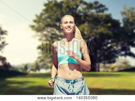 fitness, sport, friendship and healthy lifestyle concept - smiling young woman running or jogging over summer park background