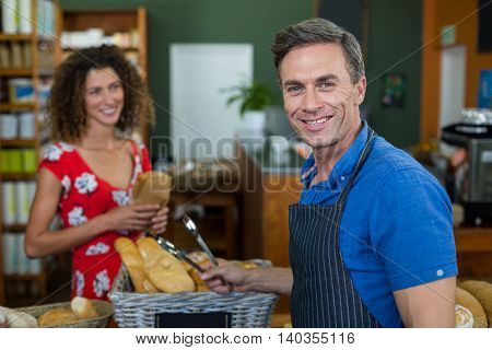 Portrait of male staff standing at bakery store counter in supermarket