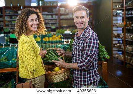 Portrait of happy couple buying vegetables in organic section of supermarket