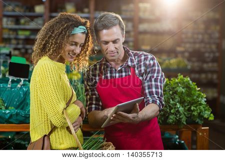 Woman looking at digital tablet used by the staff in supermarket