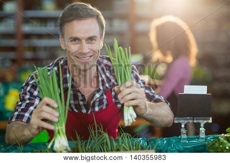 Portrait of smiling staff arranging vegetables in organic section of supermarket