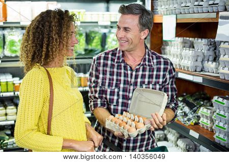 Happy couple selecting egg in supermarket