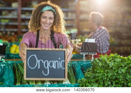 Portrait of smiling staff holding organic sign board in organic section of supermarket