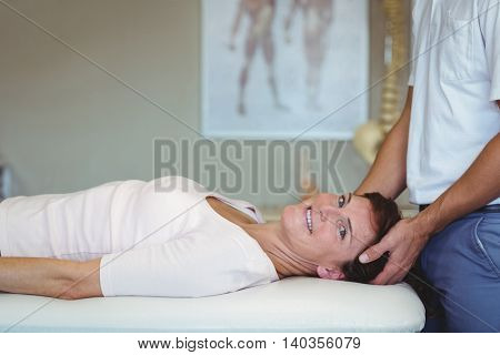 Woman receiving head massage from physiotherapist in clinic
