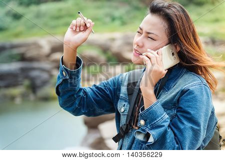 Asian women standing and talking phone outdoor.