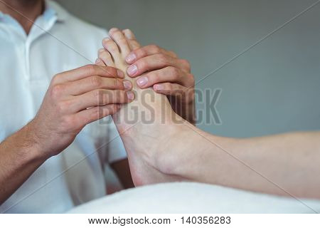 Physiotherapist giving foot massage to a woman in clinic