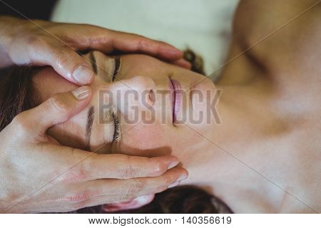 Close-up of woman receiving head massage from physiotherapist in clinic