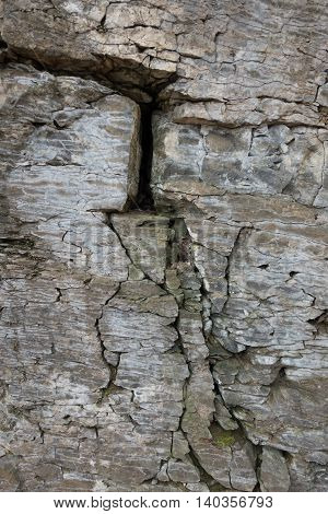 Stone wall of rock with cracks . .