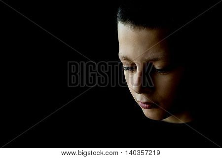Sad Boy With Tear in His Eye on a Black Background. Concept for Abuse, Bullying, Depression, Loneliness, Stress or Frustration. Little Boy Crying Isolated on Black.