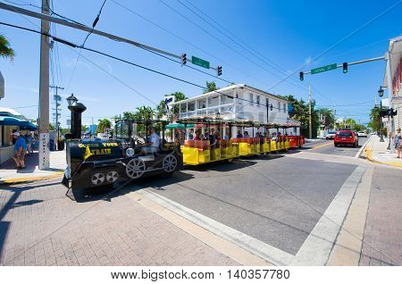 KEY WEST FLORIDA USA - MAY 02 2016: Tourists on the famous 'conch tour train' riding and sightseeing through Duval street in the center of Key West