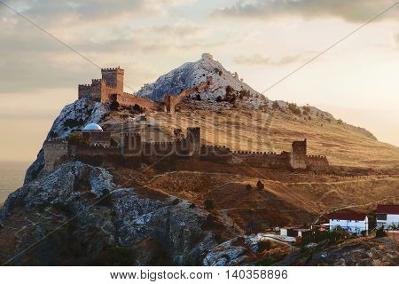 Ancient Genoese fortress in Sudak town. Panorama view at sunset. Crimea Russia.